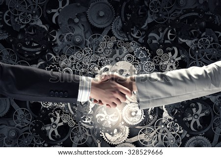 Business partners handshake and gears mechanism on background - stock photo