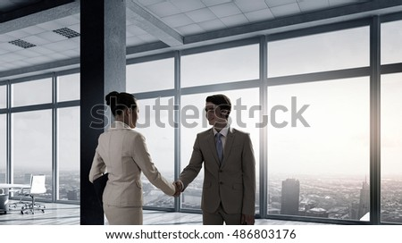 Business partners handshake . Mixed media