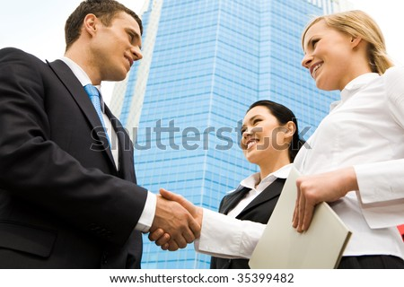 Business partners handshaking after negotiating and signing contract