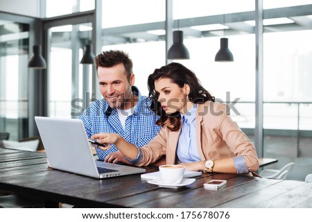 Business partners looking at the laptop display - stock photo