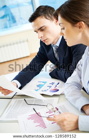 Business partners looking through papers at meeting - stock photo