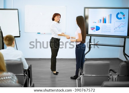business partners shake hands after a successful presentation - stock photo
