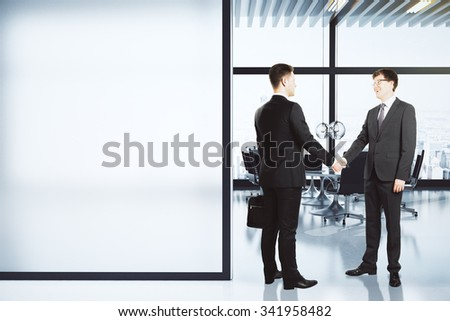 Business partners shake hands in modern conference room with blank white wall, mock up 3D Render - stock photo