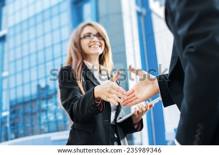Business partners shake hands, standing in front of his office. - stock photo