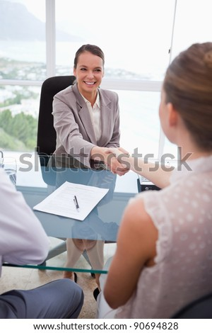Business partners shaking hands after signing contract - stock photo