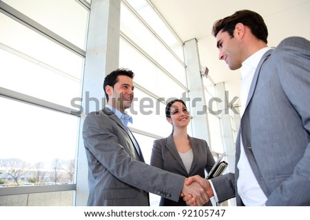 Business partners shaking hands in meeting hall - stock photo