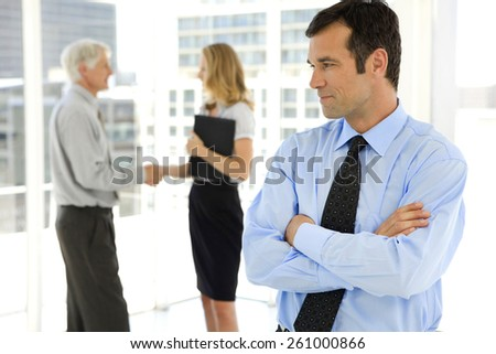 Business Partners shaking hands in the background and businessman with arms crossed looking at them on foreground - stock photo