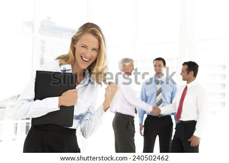 Business partners shaking hands in the background and pretty enthusiastic businesswoman looking at camera on foreground - focus on her - stock photo