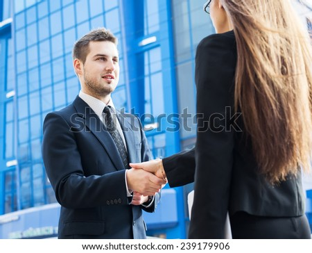 Business partners shaking hands, standing in front of his office. - stock photo