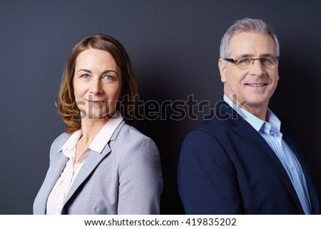 Business partners stand back to back against blue background and smile at camera while wearing open suit jackets - stock photo