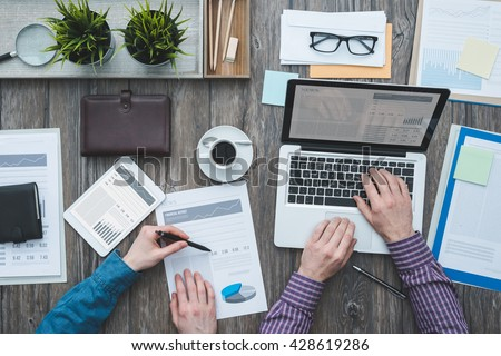 Business partners working together at office desk, they are using a laptop and checking financial reports, top view