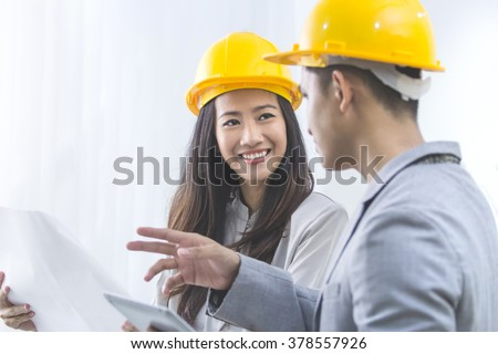 business, partnership, architecture and people concept - smiling businessman and businesswoman with blueprint and helmets discussing