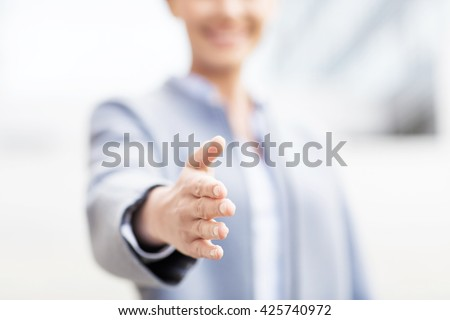 business, partnership, cooperation and people concept - close up of businesswoman giving hand for handshake over office building - stock photo