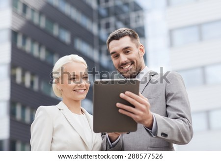 business, partnership, technology and people concept - smiling businessman and businesswoman with tablet pc computer over office building