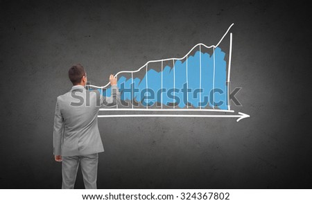 business, people, advertisement , information and office concept - businessman drawing diagram chart from back over dark gray concrete wall background - stock photo