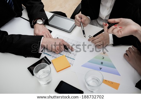 Business people analysing graphs and making notes