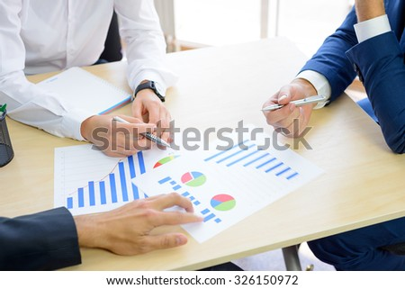 Business People Analyzing Financial Results on Graphs around the Table in Bright Modern Office. Team Work Concept - stock photo