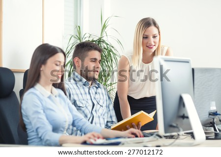 Business people analyzing their work in front of the computer - stock photo