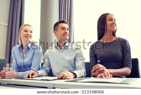 business, people and conference concept - smiling business team meeting on presentation in office