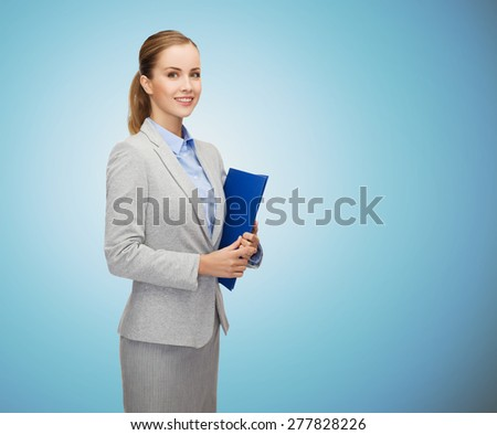 business, people and education concept - smiling young businesswoman with holding over blue background - stock photo