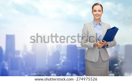 business, people and education concept - smiling young businesswoman with holding over city background - stock photo