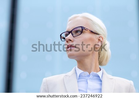 business, people and education concept - young businesswoman over office building - stock photo