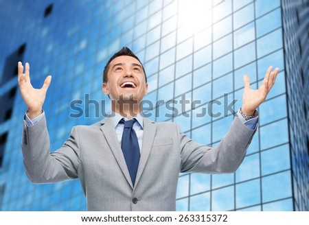 business, people and happiness concept - happy businessman in suit with raised hands laughing and looking up over office building background - stock photo