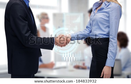business people and office concept - businessman and businesswoman shaking their hands in office - stock photo