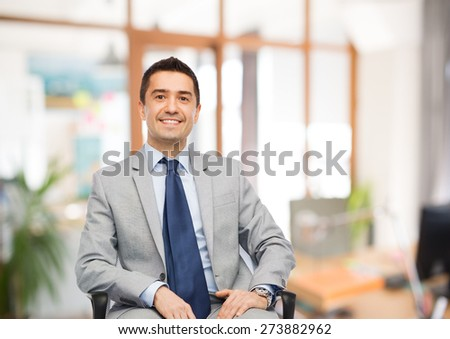 business, people and office concept - happy businessman in suit sitting in chair over office room background - stock photo
