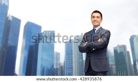 business, people and office concept - happy smiling businessman in dark grey suit over singapore city skyscrapers background - stock photo