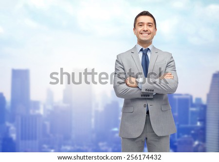 business, people and office concept - happy smiling businessman in suit over city background - stock photo