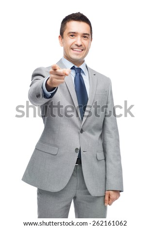 business, people and office concept - happy smiling businessman in suit pointing at you - stock photo