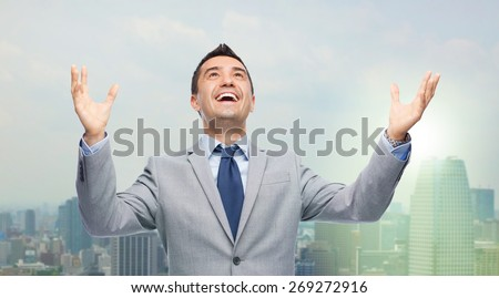 business, people and success concept - happy businessman in suit with raised hands laughing and looking up over city background - stock photo