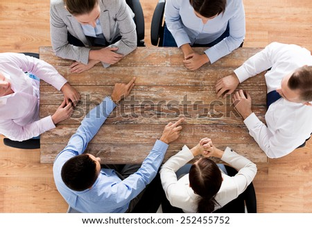 business, people and team work concept - close up of creative team sitting at table and pointing finger to something in office - stock photo