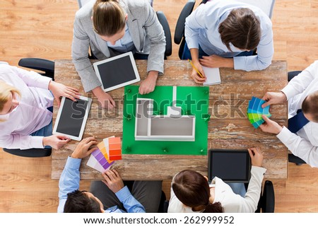 business, people and team work concept - close up of creative team with project layout, color palettes and tablet pc computers sitting at table in office - stock photo