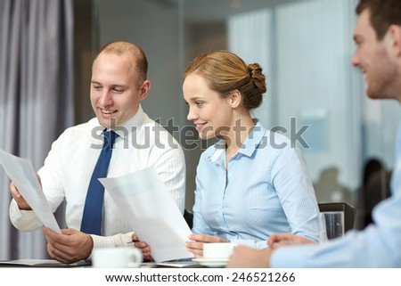 business, people and teamwork concept - smiling business team with papers meeting in office - stock photo