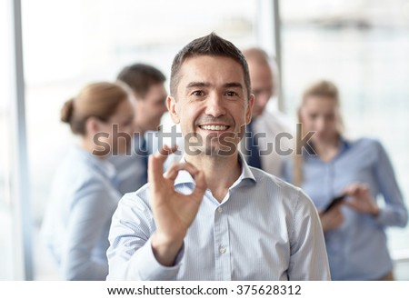 business, people and teamwork concept - smiling businessman showing ok gesture with group of businesspeople meeting in office - stock photo
