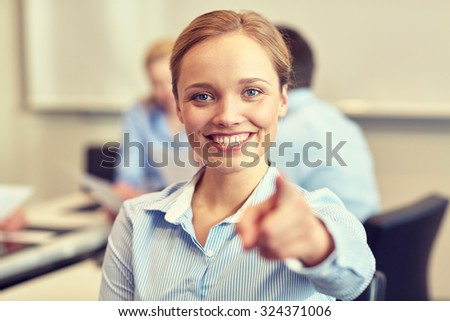 business, people and teamwork concept - smiling businesswoman pointing finger on you with group of businesspeople meeting in office - stock photo