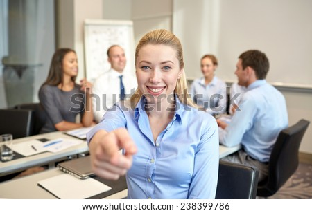 business, people and teamwork concept - smiling businesswoman pointing finger up with group of businesspeople meeting in office - stock photo