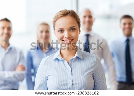 business, people and teamwork concept - smiling businesswoman with group of businesspeople in office - stock photo