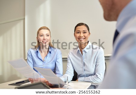 business, people and teamwork concept - smiling businesswomen meeting in office - stock photo