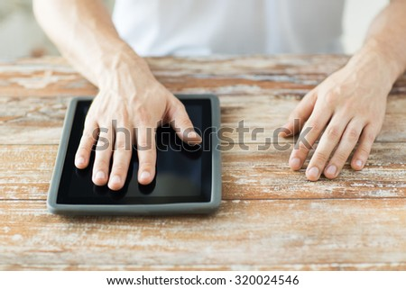 business, people and technology concept - close up of male hands with tablet pc computer on table