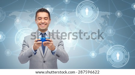 business, people and technology concept - happy businessman texting or reading message on smartphone over blue world map and network contact icons background