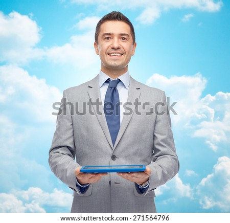 business, people and technology concept - happy smiling businessman in suit holding tablet pc computer over blue sky with clouds background - stock photo