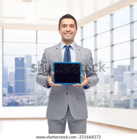 business, people and technology concept - happy smiling businessman in suit showing tablet pc computer black blank screen over city office room window background - stock photo