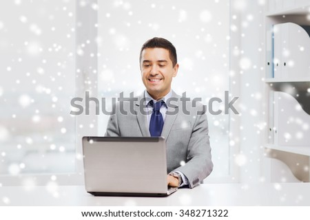 business, people and technology concept - happy smiling businessman in suit working with laptop computer in office over snow effect