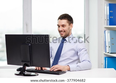 business, people and technology concept - happy young businessman with computer at office - stock photo