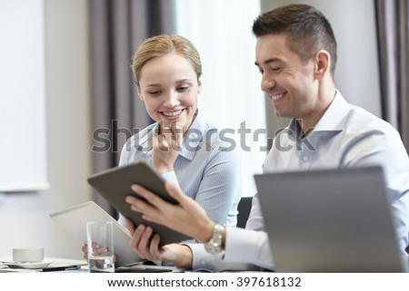 business, people and technology concept - smiling business team with tablet pc computers meeting in office - stock photo