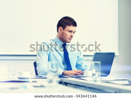 business, people and work concept - businessman with laptop computer sitting in office in front of whiteboard - stock photo