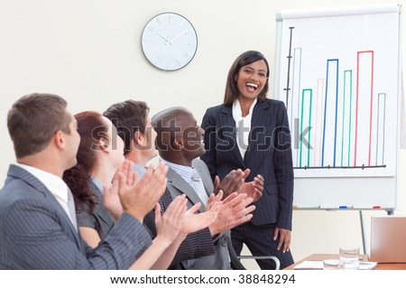 Business people applauding her colleague after giving a presentation